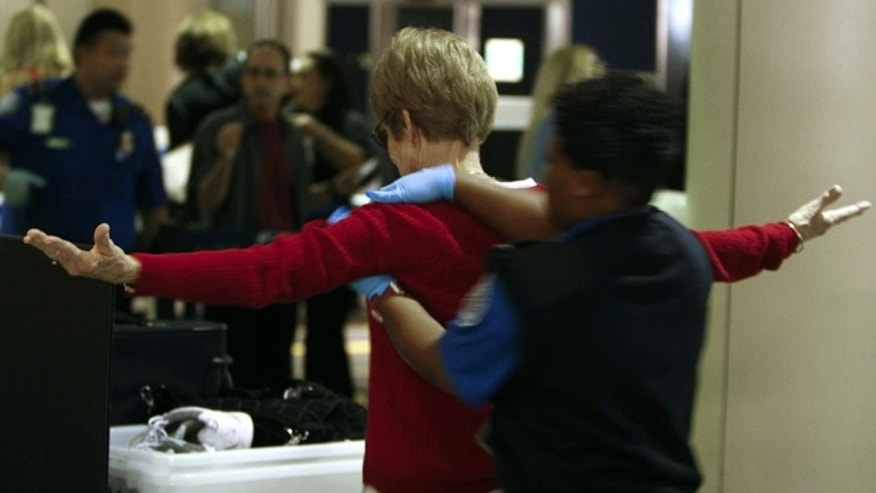 Travelers are chosen at random for a secondary inspection, while others choose the hands-on pat-down instead of the full-body scanner at one of the TSA checkpoints in Los Angeles International Airport's Terminal One in Los Angeles.