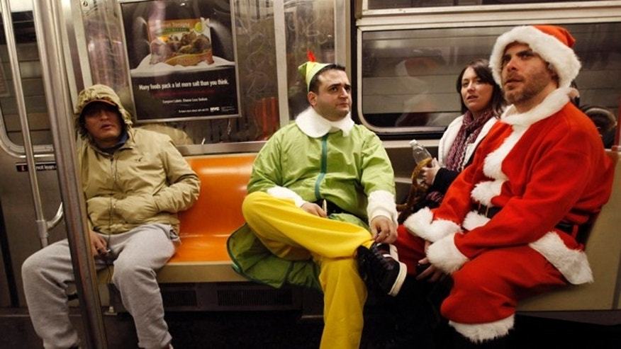 Dec. 11, 2010: John Paul, center, of Manhattan, dressed as an Elf and Michael Smallwood, of Brooklyn, dressed as Santa ride the E train downtown in New York for the annual SantaCon pub crawl where participants dress up in Santa and other Christmas themed outfits.