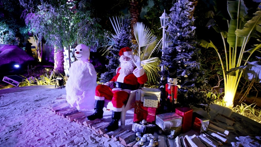 In this Friday, Dec. 20, 2013 photo, a man dressed as Santa Claus waits for guests to join him for a photograph during a Christmas party in Dubai, United Arab Emirates. The Middle East's brashest city is increasingly embracing the trappings of Christmas in a way that would be unthinkable in more conservative parts of the Muslim world. Christmas trees adorn shopping centers and residential neighborhoods, and high-end hotels try to outdo one another with extravagant and boozy holiday dinners. (AP Photo/Kamran Jebreili)