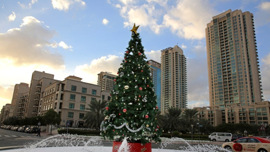 In this Saturday, Dec. 21, 2013 photo, a large Christmas tree with fake snow around it, is showcased on a street in Dubai, United Arab Emirates. The Middle East's brashest city is increasingly embracing the trappings of Christmas in a way that would be unthinkable in more conservative parts of the Muslim world. Christmas trees adorn shopping centers and residential neighborhoods, and high-end hotels try to outdo one another with extravagant and boozy holiday dinners. (AP Photo/Kamran Jebreili)