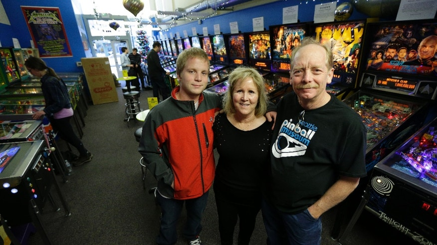 Dec. 16, 2013: Charles Martin, right, poses for a photo with his wife Cindy, center, and their son Michael, left, on the main level of the Seattle Pinball Museum in Seattle.