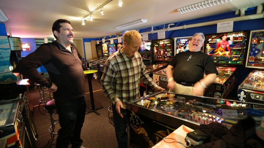Dec. 16, 2013: Visitors Jeff Goldsmith, left, Jim Lindquist, center, and Dave Socha, right, play the PIN BOT pinball machine, which was released in 1986, as they visit the Seattle Pinball Museum in Seattle.