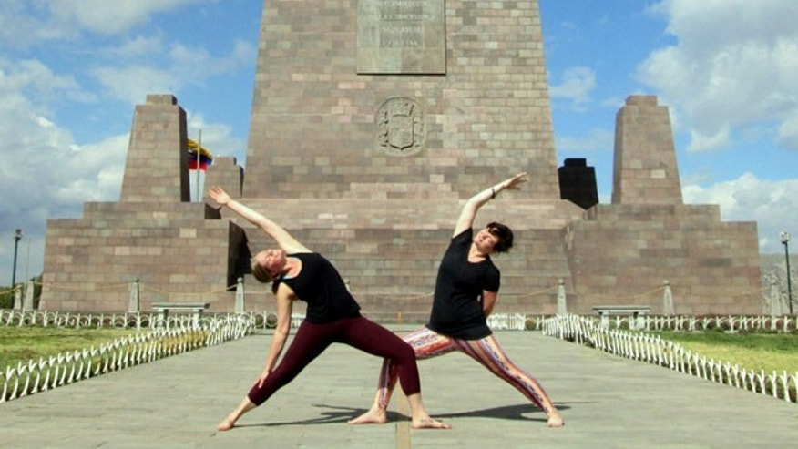 Two yogis pose in both the Northern and Southern hemispheres on the Equator in Ecuador.