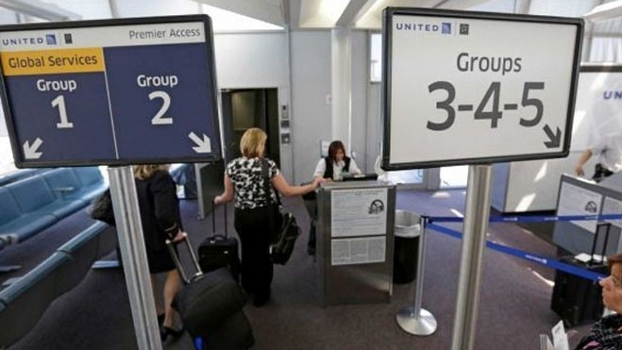 United Airlines passengers board a flight using the Premier Access line at O'Hare International Airport in Chicago.