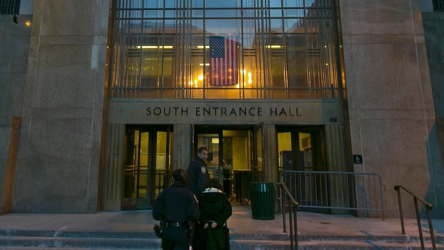 March 11, 2014: Two police officers escort a handcuffed woman into New York's Criminal Court Building, Tuesday evening,