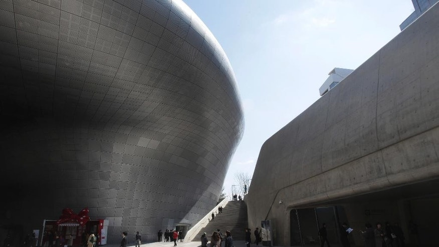 March 21, 2014: Visitors are dwarfed by Dongdaemun Design Plaza in Seoul, South Korea.