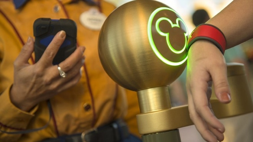 A Walt Disney World Resort guest uses a MagicBand to enter Magic Kingdom theme park in Lake Buena Vista, Fla.
