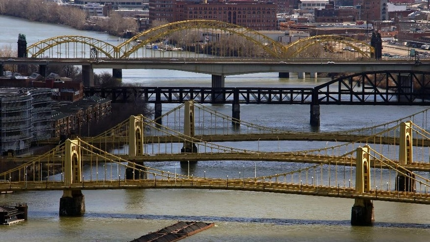 A towboat and barges make their way up the Allegheny River under three historic bridges.