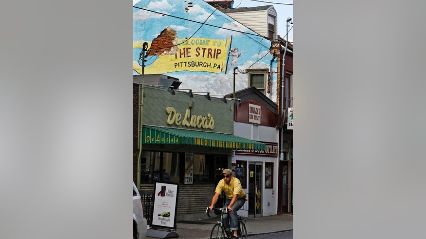 A bicyclist rides by some of the mom-and-pop restaurants and shops on Penn Avenue in Pittsburgh's Strip District.