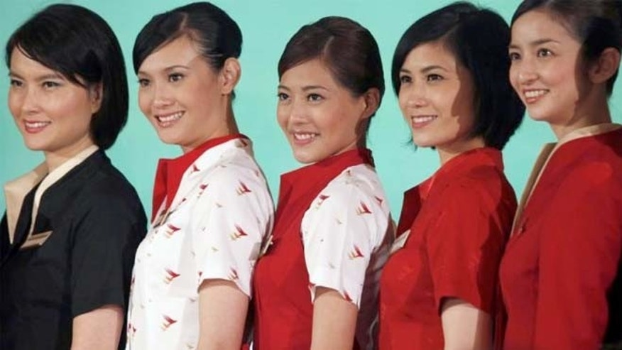 Flights attendants present their new uniforms during a news conference in Hong Kong in 2013.