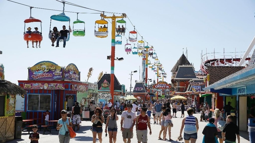 April 7, 2014: People walk below the Sky Glider and make their way along the Santa Cruz Beach Boardwalk in Santa Cruz, Calif.