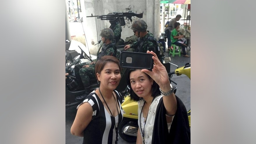 Residents stop to take a photograph of themselves at a military checkpoint in central Bangkok, Thailand, Tuesday, May 20, 2014.