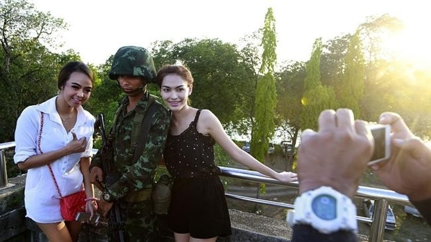 Passers-by with a soldier near a pro-government rally on the outskirts of Bangkok
