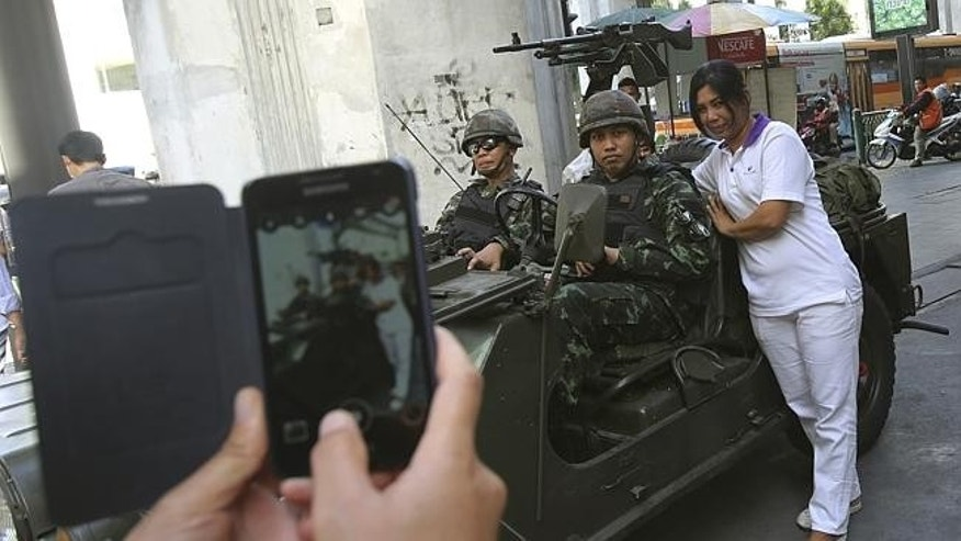 A woman poses by an armored car.