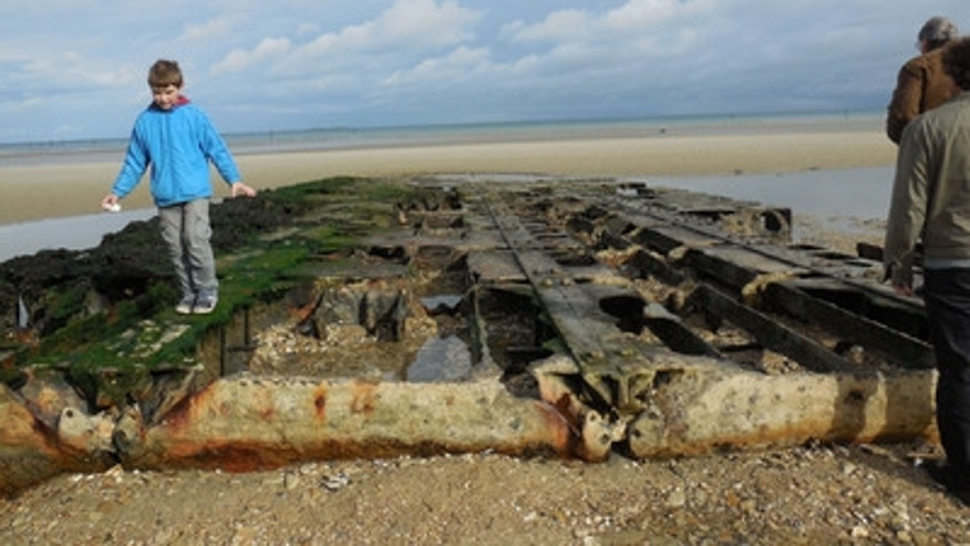 At Utah Beach, a kid plays on a remnant of the temporary harbor built after the invasion to bring supplies to the troops.