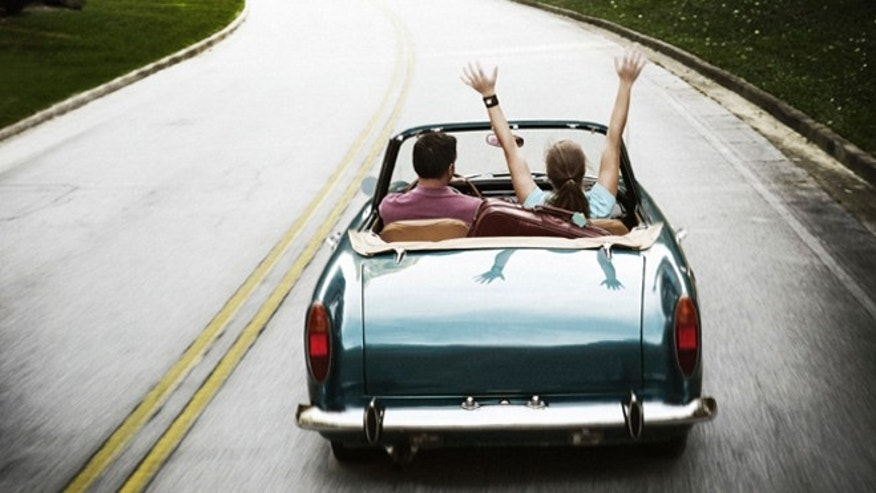 Couple taking a road trip in vintage car.