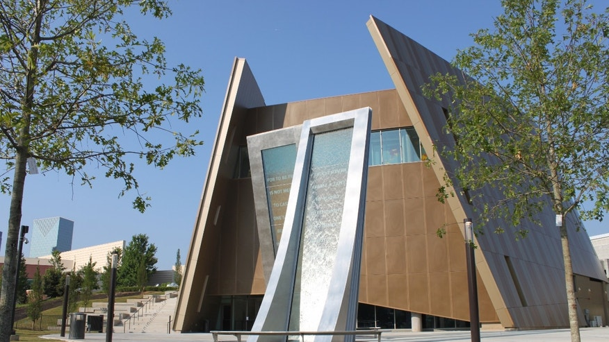 The exterior of the building has soaring, arced sides resemble a pair of cupped hands, and a grass-covered rooftop.