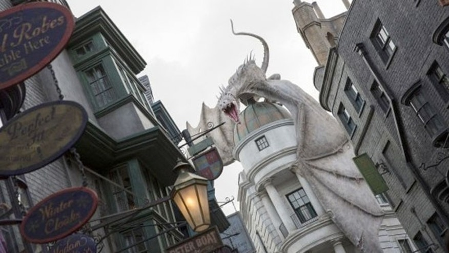 A realistic-looking fire-breathing dragon is perched atop Gringotts Bank at the end of Diagon Alley.