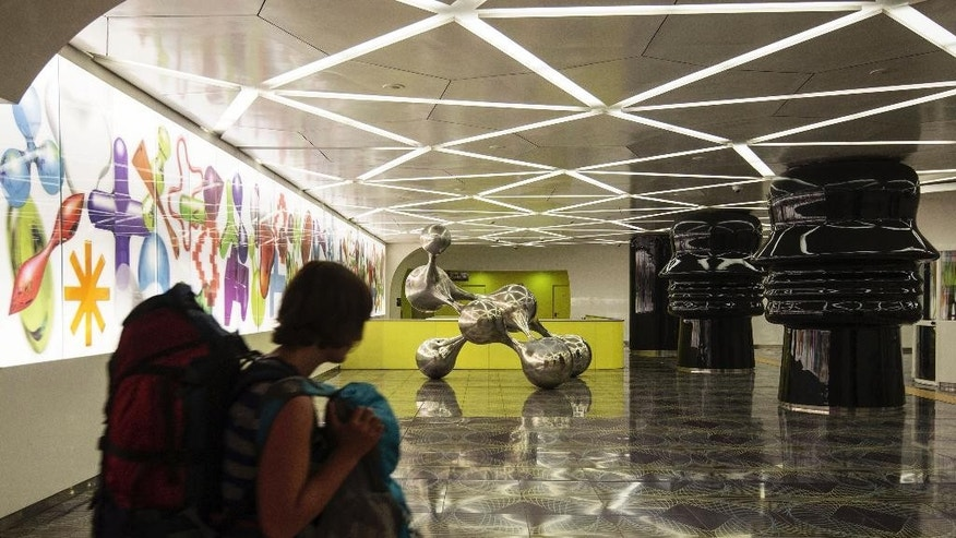 A woman walks past sculptures by Egyptian architect Karim Rashid on display in the underground metro station of Universita'.