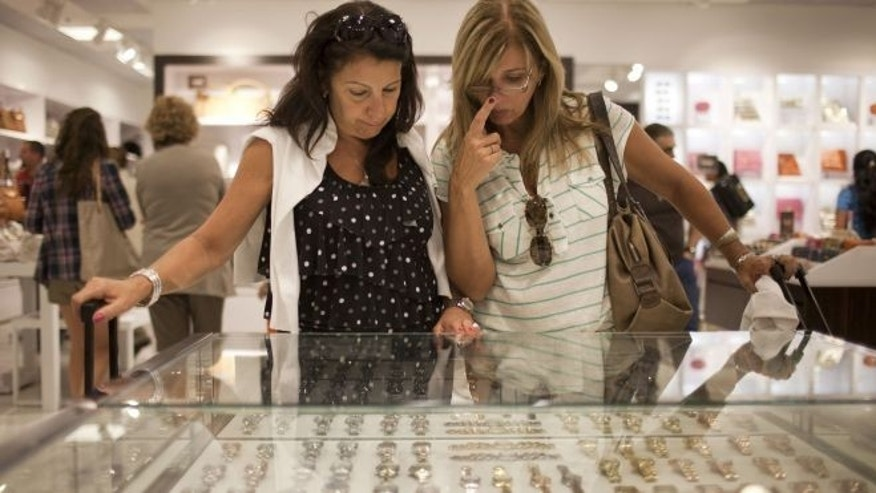 Beatriz Cesari, left, and her friend Sylvia Schleier, from Sao Paulo, Brazil, look at watches as they shop in Florida.