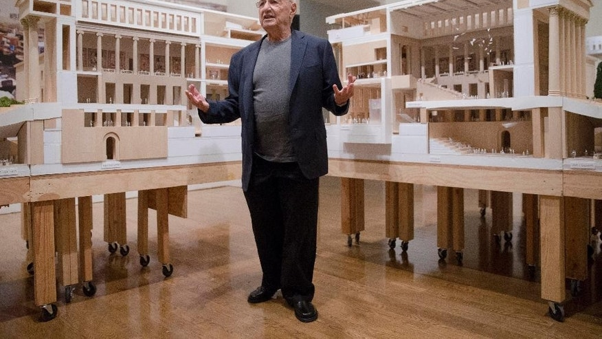 Architect Frank Gehry poses for photographs in front of a model that helps illustrate the Philadelphia Museum of Art's master plan.