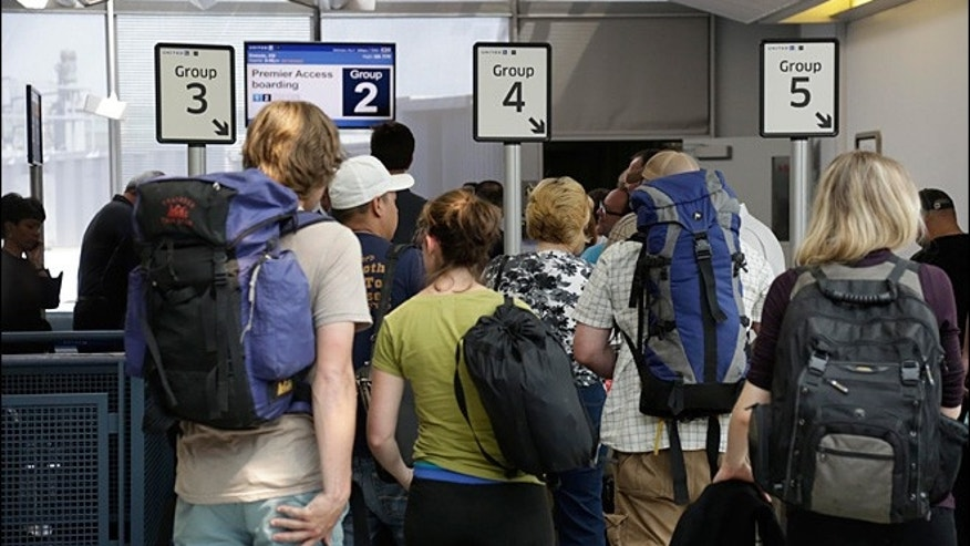 Groups of passengers wait at a United Airlines gate.