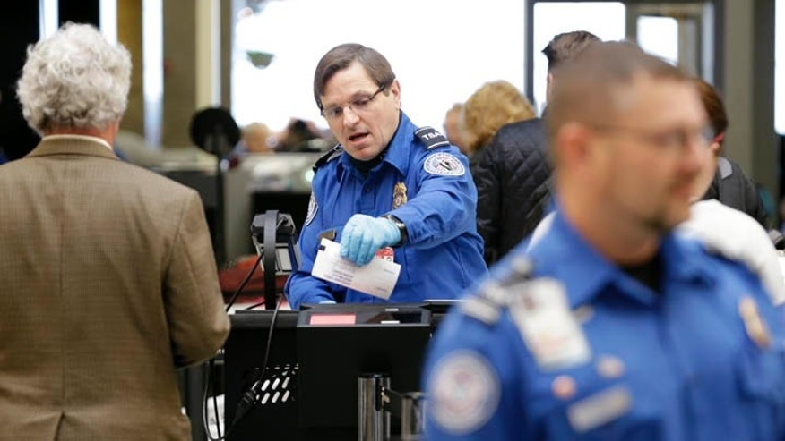 TSA agent checks a passenger ticket.