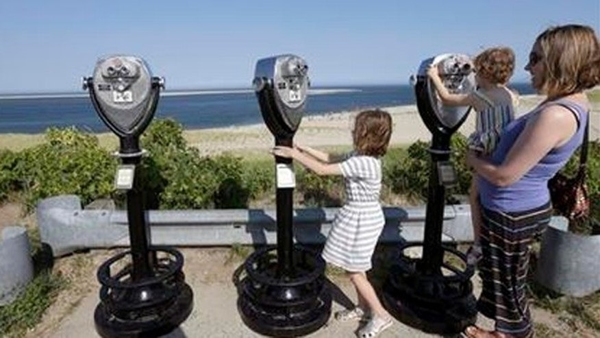 Molly Saint-James, of Baltimore, right, helps her daughters Ellie McDonald, left, 6, and Poppy McDonald, 3, use telescopic viewers overlooking a beach while on vacation in Chatham, Mass.