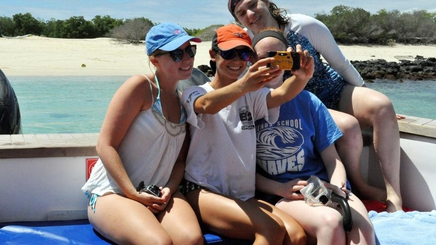 FILE: A group of American high school students, from left,  Isabela Gettier, Elizabeth Thomas, Hannah Whitt Linsly  and Stephanie Kirby posing for a group selfie on a trip to the Galapagos.