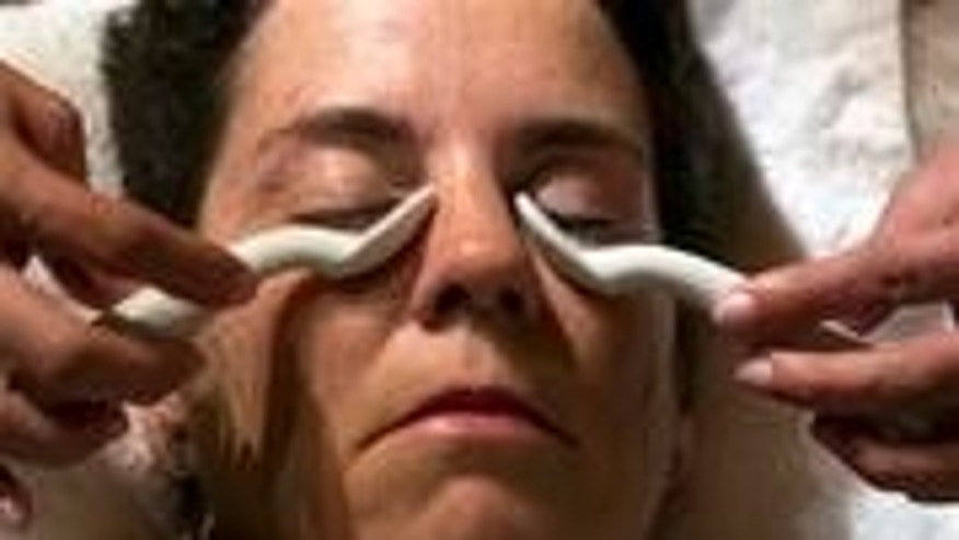 To soothe puffy eyes, cold Limoges porcelain spoons are applied to a woman's face, a treatment from The Spa at The Hotel Hershey, Hershey, Pa.