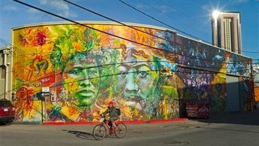 "This July 12, 2014 photo shows a bicyclist riding past a mural depicting the portraits of Hawaiian Queen Liliuokalani and King David Kalakaua, in Honolulu.  The urban art piece is a collaboration between Native Hawaiian artists Solomon Enos and John ""Prime"" Hina along with Baltimore based artists Gaia. Honolulu is famous for golden sand beaches and big waves. But the citys warehouse district, called Kakaako, is famous for its thriving urban arts scene, with colorful street murals so big they stretch across walls and sometimes entire sides of buildings. Honolulu artist Jasper Wong sought to revitalize the area with urban art. Wong created a group called POW!WOW! Hawaii with the goal of beautifying Kakaako and bringing people together through art.  Artists from around the globe participated, painting murals on walls across the decaying neighborhood.  (AP Photo/Marco Garcia)"