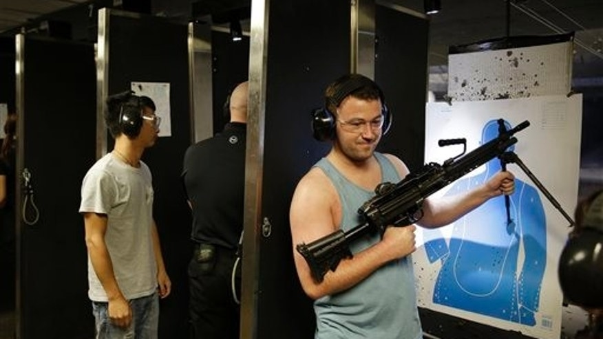 Ryan Doherty holds up a fully automatic machine gun after firing it at Machine Guns Vegas Thursday, Aug. 28, 2014, in Las Vegas.  Most visitors to Machine Guns Vegas have already pulled the trigger on an Uzi or an M5, from the behind the controls of their XBox. But with strict gun laws keeping the real thing out of reach for most people, especially outside the U.S., indoor shooting ranges with high-powered weapons have become a hot tourist attraction. (AP Photo/John Locher)