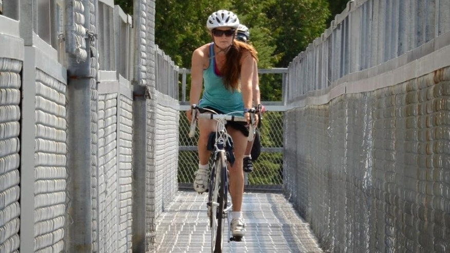 Aug. 11, 2014: Ariane Ste-Marie of Equinox Aventure leading a cyclist across a dam on Quebec's Veloroute des Bleuets, the Blueberry Trail, approaching Alma.