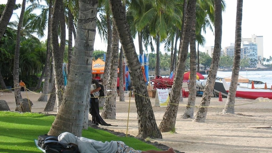 Sept. 8, 2014: A man sleeps near a surf board rental stand at Waikiki Beach in Honolulu.
