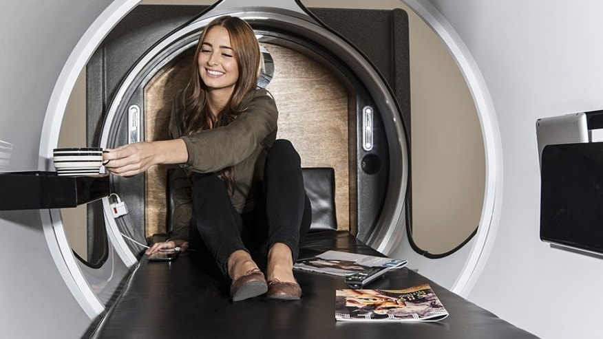 The pod interior features outlets and storage for books and devices.