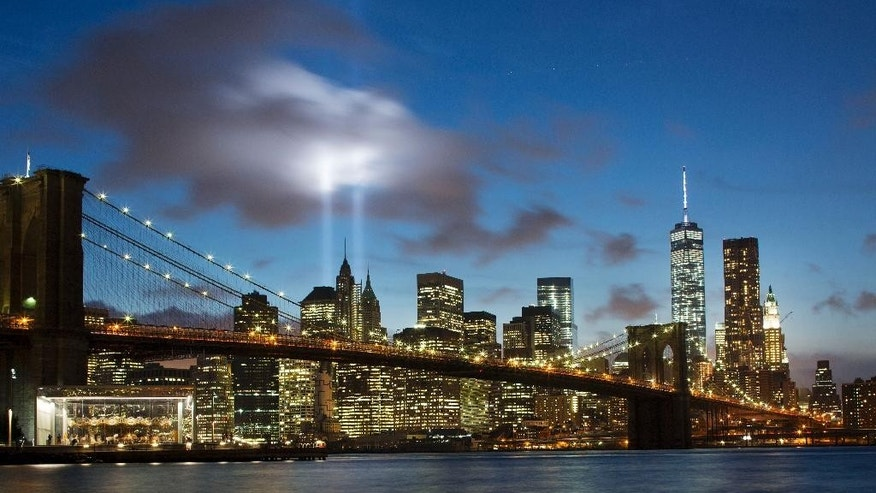 FILE - Tribute in Light rises behind the Brooklyn Bridge and buildings adjacent to the World Trade Center complex in New York.