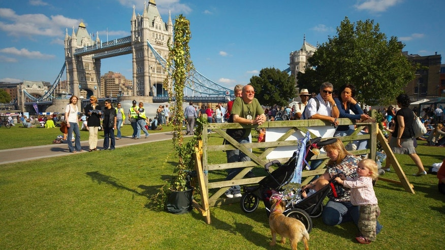 Families sitting in the sunshine on the Southbank, Tower Bridge in background.