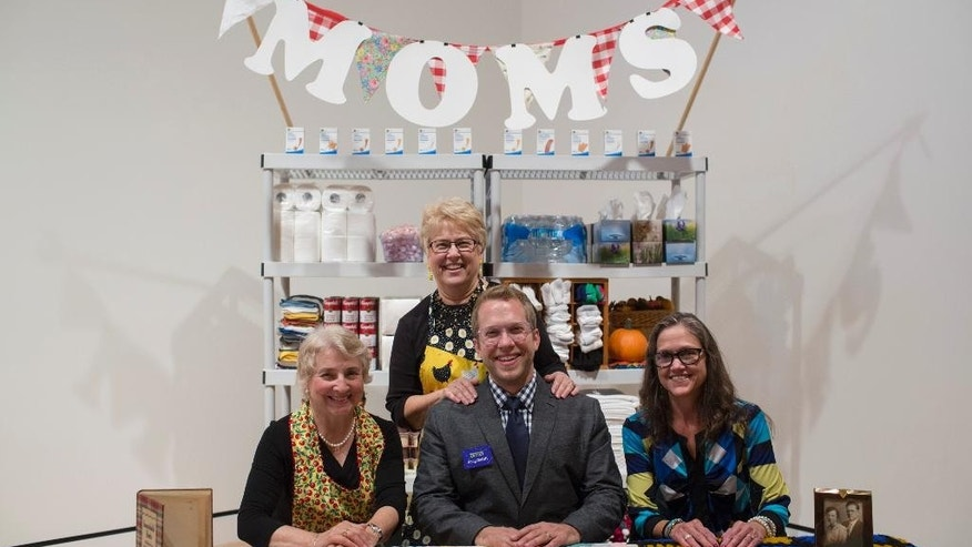 September 2014: Artist Andy Ducett with his mom Marilyn behind him and two volunteers at the Mom Booth at the museum in Bentonville, Ark.