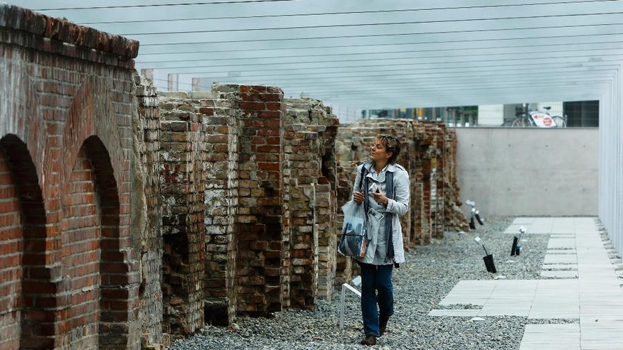FILE: A woman inspecting original remains of the historical Gestapo and SS buildings at the new documentation center Topography of Terror in Berlin.