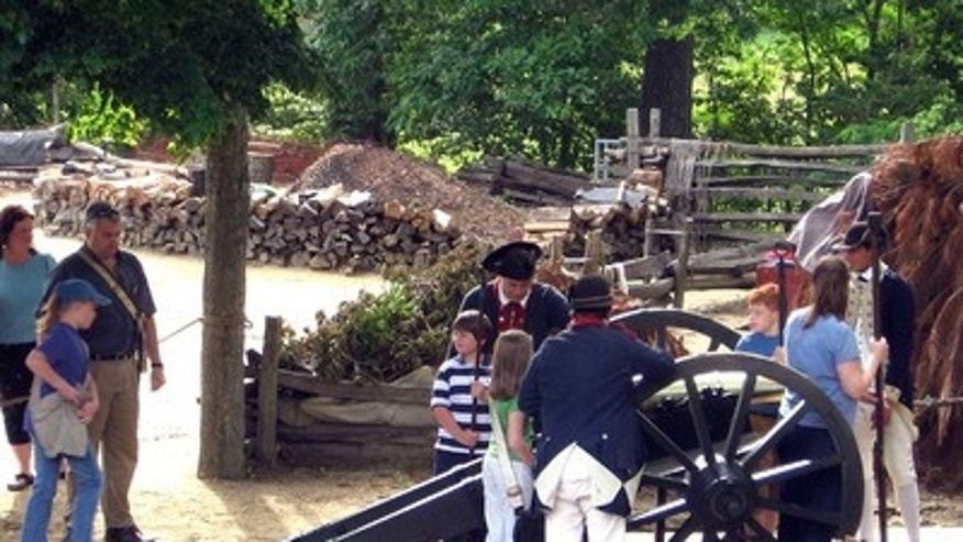 Continental Army encampment, cannon demonstration with visitors.