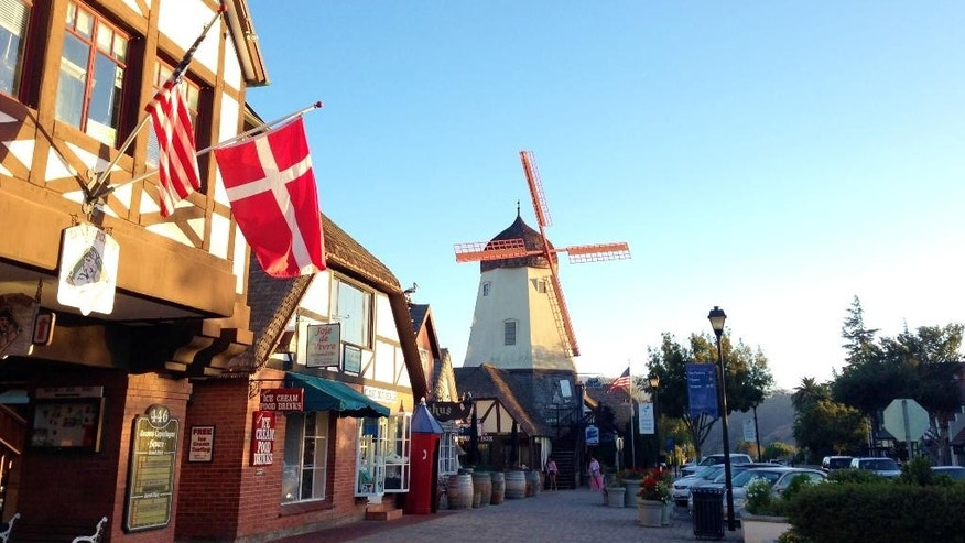 This Sept. 30, 2014 photo shows the Danish flag flying on Alisal Road in Solvang, Calif., with a windmill in the background. Founded in 1911 by Danish immigrants, Solvang is a touristy enclave with Danish bakeries, Danish-themed hotels and even a Hans Christian Andersen Museum. (AP Photo/Solvej Schou)
