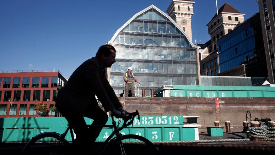 A man rides on a bicycle along the Ourcq canal, in Pantin, east of Paris, Wednesday, Nov. 12, 2014.  Pantin, a once-gritty Paris suburb, is sometimes compared to Brooklyn, New York. Both areas have gentrified, with artists and galleries moving in to old warehouses and real estate prices shooting up. Many other neighborhoods and cities around the world also compare themselves to Brooklyn, which has become known for hipster culture and artisanal food.  (AP Photo/Thibault Camus)