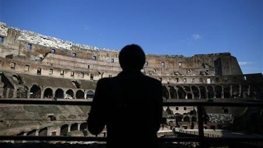 A tourist is silhouetted against Rome's Colosseum.