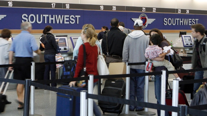 FILE: People wait in line at the Southwest Airlines ticket counter at Midway International airport in Chicago.