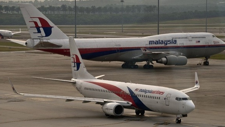 A Malaysia Airlines Boeing-737 plane taxis past a 747 (back) from the same company at the Kuala Lumpur International Airport in Sepang on June 17, 2014.  Malaysia's government pledged on June 16 it 'will not rest' until missing flight MH370 is found but relatives said on the 100th day since the plane's disappearance that they wanted answers, not more promises.   AFP PHOTO / Manan VATSYAYANA        (Photo credit should read MANAN VATSYAYANA/AFP/Getty Images)