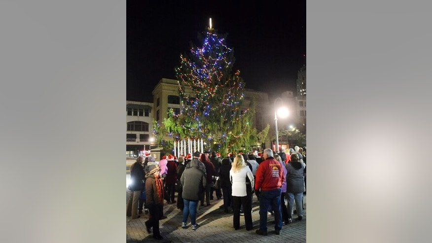Reading residents look on during the Christmas tree lighting Friday in Reading. Reading's spindly 50-foot spruce drew the ire of residents who said it was ruining their holiday spirit.