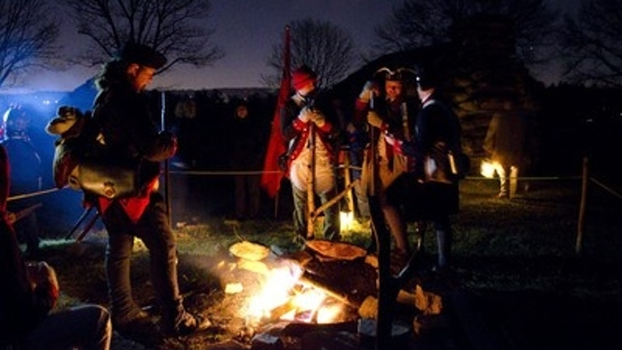 Revolutionary War Re-enactors gather around a campfire at Valley Forge National Historical Park.