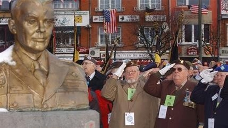 In this Dec. 18, 2004 file photo, U.S. and Belgian World War II veterans salute during a wreath laying ceremony at the General Anthony C. McAuliffe memorial in Bastogne, Belgium.