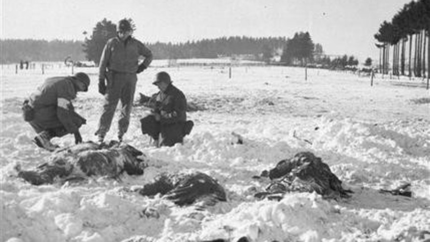 In this Jan/ 1945 file photo, American soldiers check for identification on the bodies of dead U.S. troops shot by the Germans near Malmedy, Belgium during World War II's Battle of the Bulge. The Battle of the Bulge was one of the largest and bloodiest battles of World War II. A tour taking place in December 2014 thats connected to the National World War II Museum in New Orleans is taking three dozen people to the battlefields and towns in Belgium where the Battle of the Bulge was fought 70 years ago.
