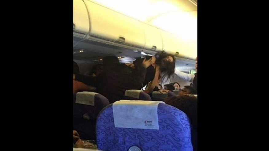 A woman is seen hitting her head on the overhead compartment during an argument mid-air.